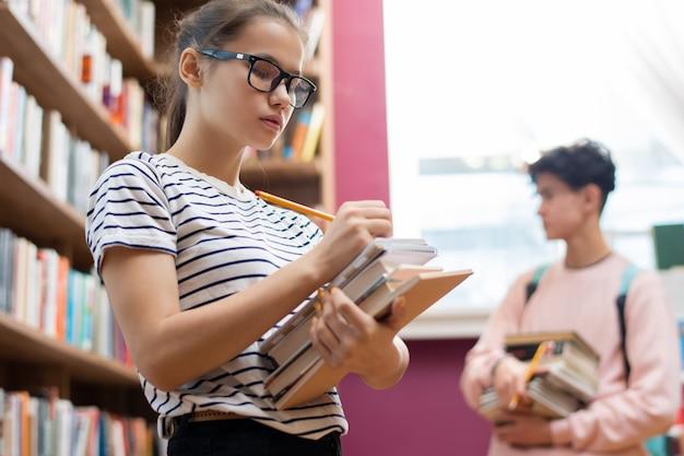Sprytny nastolatek w okularach robi notatki w notatniku na stosie książek, stojąc przy półce z książkami w bibliotece