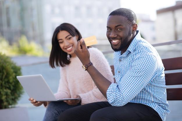 Sprytny, oddany i innowacyjny mężczyzna spędza dzień ze swoją dziewczyną na świeżym powietrzu i płaci kartą kredytową za towary, które wybiera online