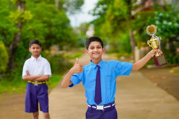 Sprytny uczeń podnosi trofeum jako zwycięzca w szkolnym konkursie i świętuje ze swoim przyjacielem.