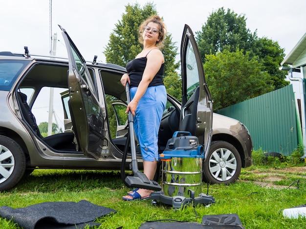 Sprząta autko, dziewczyna zbiera okruchy odkurzaczem w aucie
