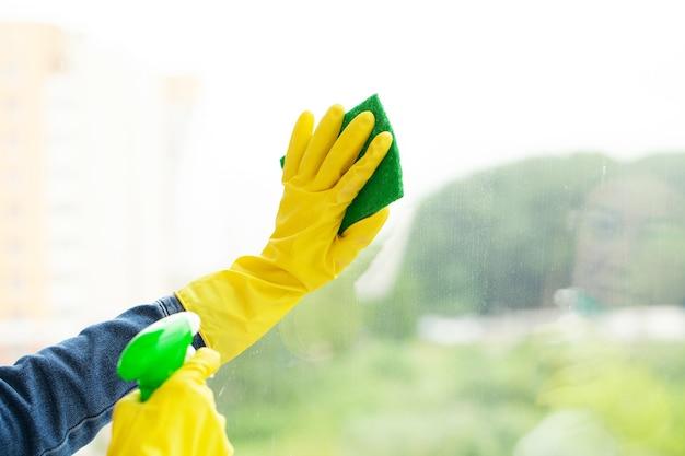 Sprzątaczka czyści sprzątanie w biurze mokrą szmatką.