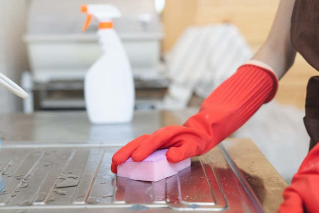 Sprzątaczka pokojówka sprzątanie w kuchni z gąbki i do mycia.