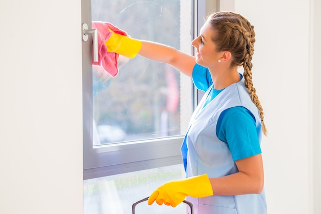 Sprzątaczka szmatką w oknie