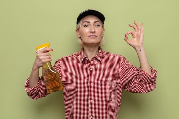 Sprzątaczka w kraciastej koszuli i czapce, trzymająca spray do czyszczenia, patrząca z pewną siebie miną, robiąca znak ok