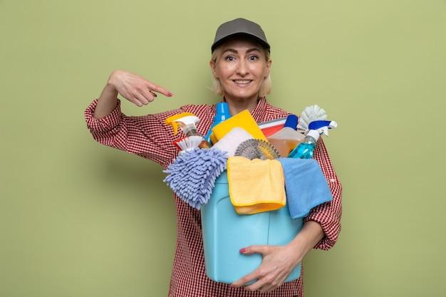Sprzątaczka w kraciastej koszuli i czapce, trzymająca wiadro z narzędziami do czyszczenia, wskazująca na nie palcem wskazującym, uśmiechnięta radośnie