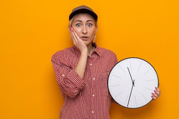 Sprzątaczka w kraciastej koszuli i czapce, trzymająca zegar patrząc w kamerę zdezorientowana i zmartwiona, stojąca na pomarańczowym tle