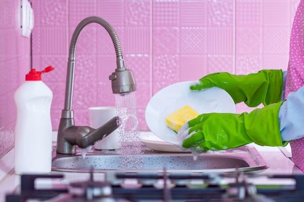 Sprzątaczka w zielonych gumowych rękawiczkach i fartuchu myje naczynia gąbką i detergentem w kuchni w domu