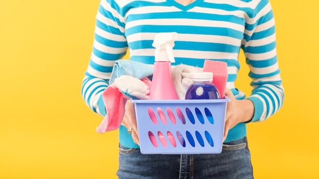 Sprzątanie domu. podstawowy zestaw do czyszczenia. kobieta trzyma kosz zaopatrzenia. skopiuj miejsce na żółtej ścianie.