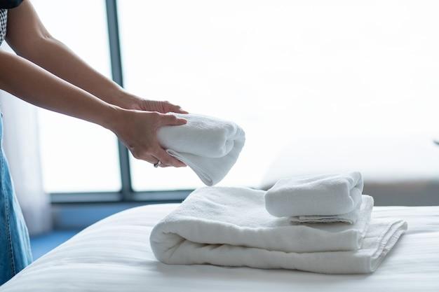 Sprzątanie hotelu, ręcznik kąpielowy na białym łóżku, obsługa pokoju?