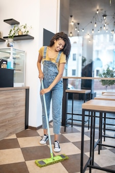 Sprzątanie, kawiarnia. uśmiechnięta młoda kobieta w dżinsowych kombinezonach z mopem stojącym w kawiarni mycie podłogi