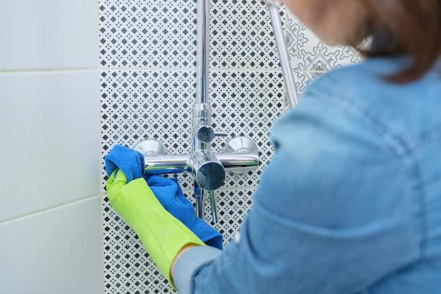 Sprzątanie łazienki, kobieta w rękawiczkach z szmatką i detergentem, prysznic do mycia i polerowania