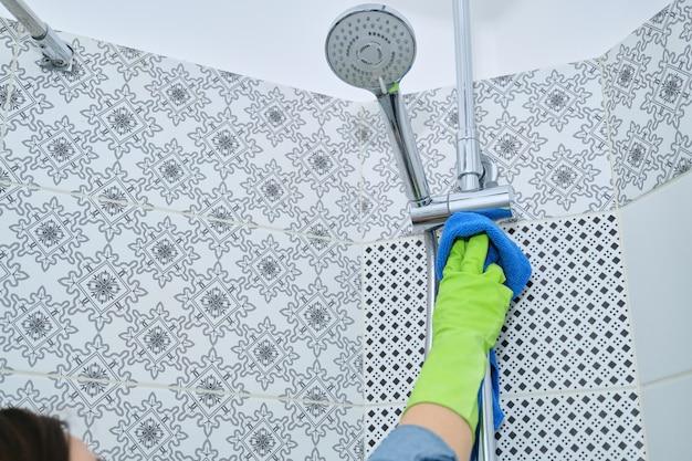 Sprzątanie łazienki, kobieta w rękawiczkach z szmatką i detergentem