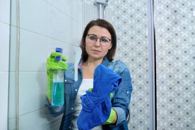 Sprzątanie łazienki, kobieta w rękawiczkach ze szmatką i detergentem, mycie i polerowanie szkła prysznicowego