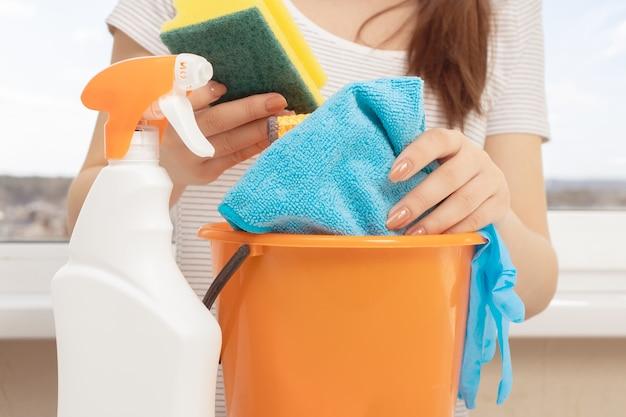 Sprzątanie mieszkań, biur, domków, magazynów, garaży. młoda dziewczyna z produktami do czyszczenia wanien, zlewów, toalet, gąbek i szmat