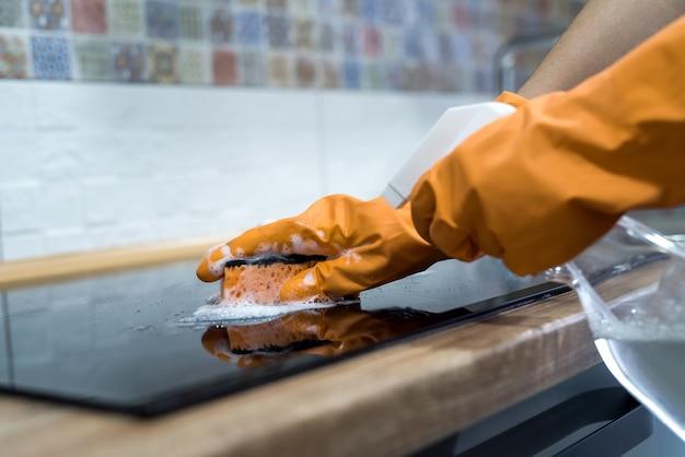 Sprzątanie nowoczesnej szklanej ceramicznej powierzchni elektrycznej za pomocą gąbki w swojej kuchni. prace domowe