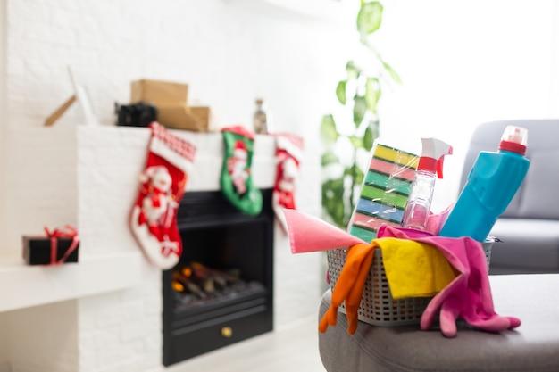 Sprzątanie przed bożym narodzeniem. wielokolorowe środki czystości. gąbki, szmaty i spray ze świątecznymi dekoracjami na tle nowoczesnego domu