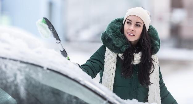 Sprzątanie samochodu ze śniegu w zimowy dzień przez kobietę-kierowcę.