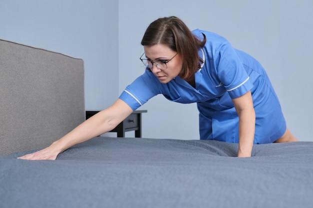 Sprzątanie w pokoju hotelowym, profesjonalna pokojówka w średnim wieku przygotowująca pokój gościnny, ścielenie łóżka, miejsce do kopiowania