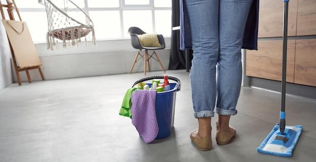 Sprzątanie widok z tyłu sprzątaczki z mopem i plastikowym wiaderkiem ze szmatami, detergentami i?