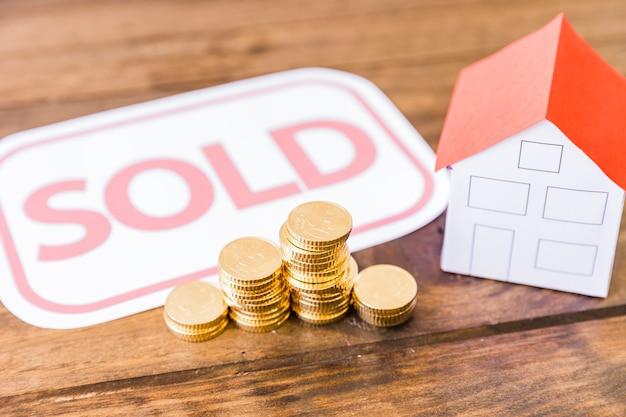 Sprzedająca etykietka z brogować monetami i domem na drewnianym biurku