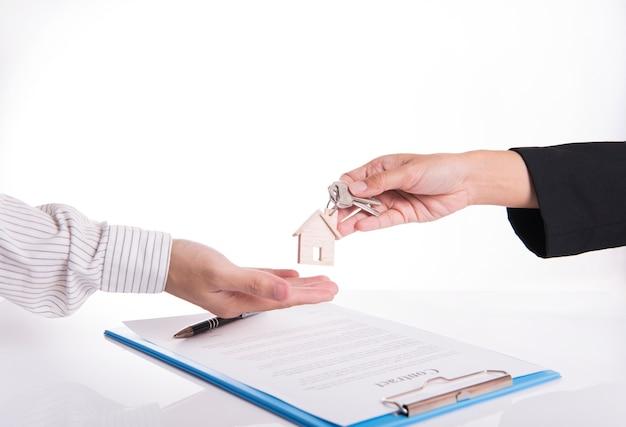 Sprzedawca agent wymiana klucz dom z klientem po umowy umowy sprzedaży domu.