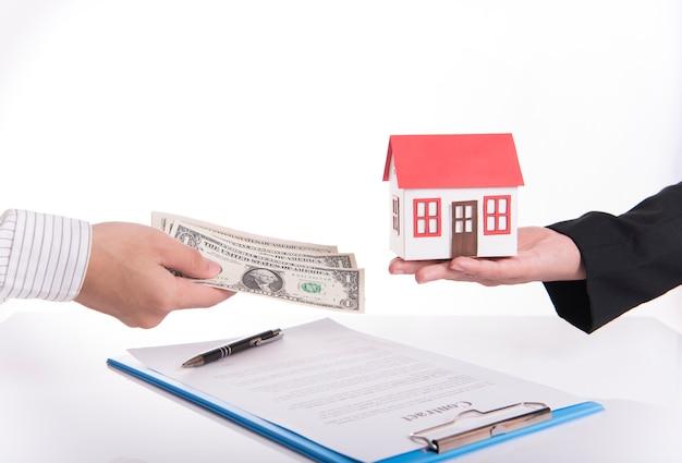 Sprzedawca agent wymieniać dom i pieniądze z klientem po umowie umowy sprzedaży domu