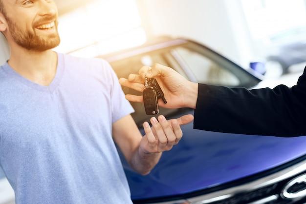 Sprzedawca dał kupującemu kluczyki do samochodu.