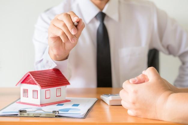 Sprzedawca domu rozciąga się trzymając czarny długopis,