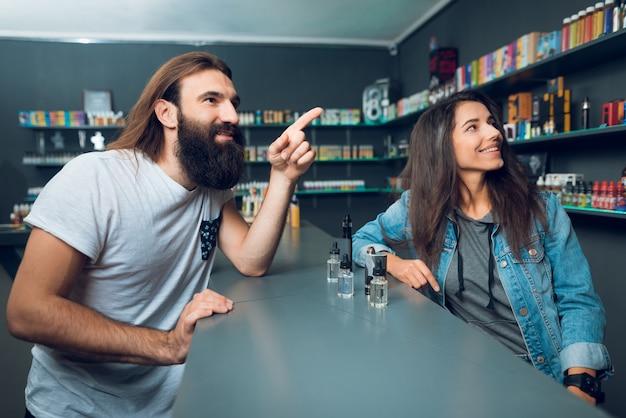 Sprzedawca dziewczyna pokazuje wybór elektronicznego papierosa.