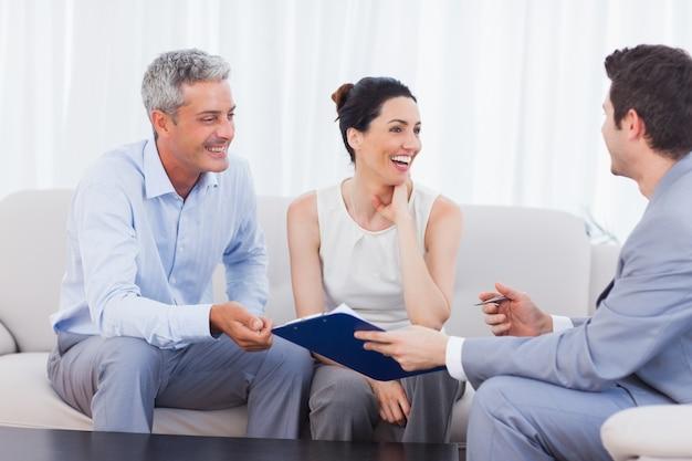 Sprzedawca i klienci rozmawiają i śmieją się razem na kanapie
