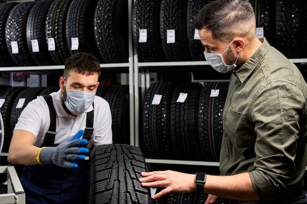 Sprzedawca i klient na stoisku z maskami medycznymi omawiają opony samochodowe, sprzedaż opon samochodowych podczas pandemii koronawirusa