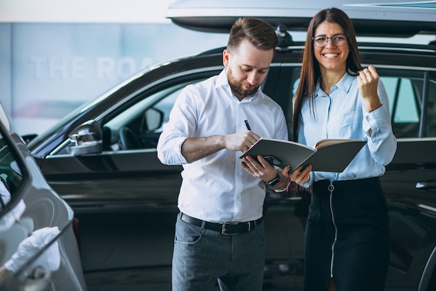 Sprzedawca i kobieta szuka samochodu w salonie samochodowym
