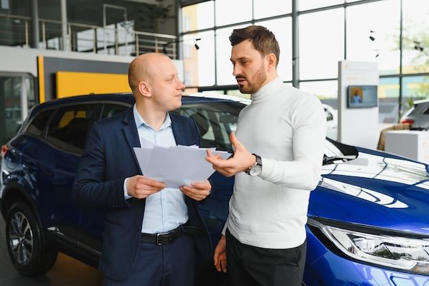 Sprzedawca i kupujący w salonie samochodowym
