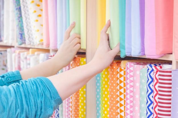 Sprzedawca i kupujący wybierają materiał w sklepie. półki z tkanin bawełnianych, kolorowe pastelowe kolory.