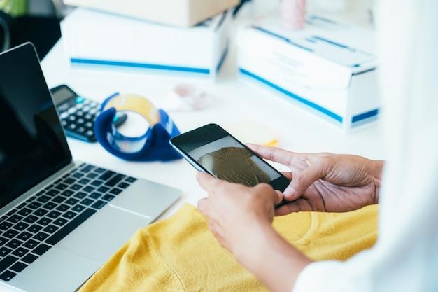 Sprzedawca internetowy korzysta z telefonu komórkowego, aby zrobić zdjęcie produktu