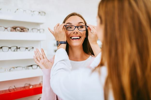 Sprzedawca kobiet w średnim wieku i klient wybierający nowe okulary w nowoczesnym sklepie optycznym. koncepcja zakupów.