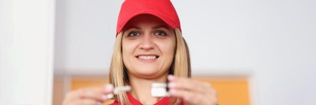 Sprzedawca kobieta trzyma dziurkę od klucza i rdzeń zamka