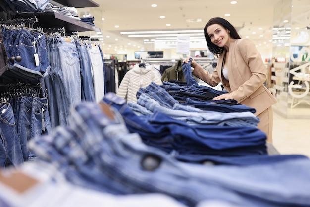 Sprzedawca kobieta układa dżinsy w oknie sklepu