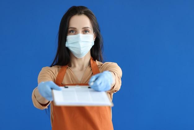Sprzedawca kobieta w masce ochronnej i rękawiczkach dająca schowek z dokumentami do podpisu