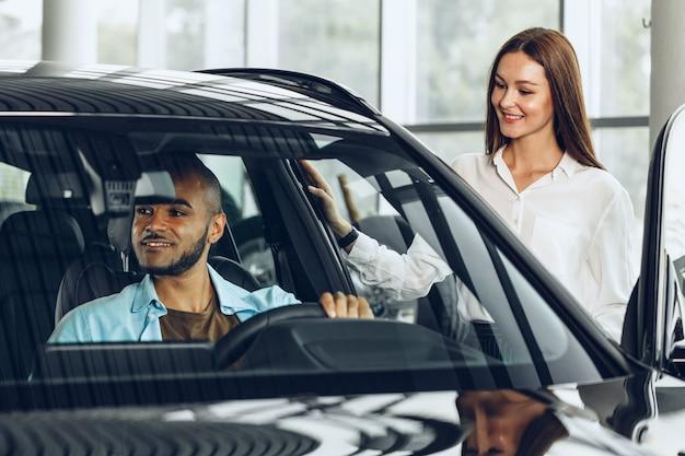 Sprzedawca młoda kobieta w salonie samochodowym pokazując samochód swojemu klientowi płci męskiej