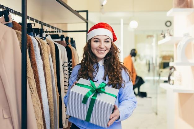 Sprzedawca oferuje świąteczny prezent dla sklepu odzieżowego w świątecznych ubraniach