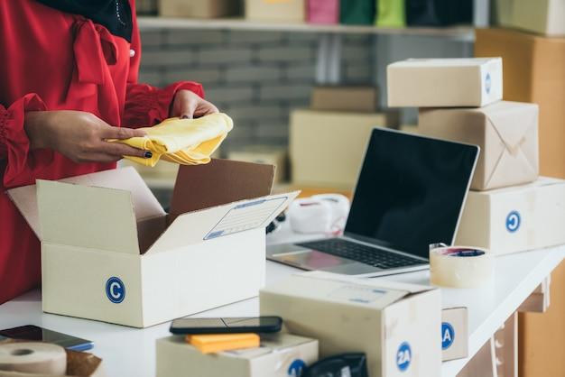 Sprzedawca online pracuje w domowym biurze i pakuje paczkę wysyłkową do klienta.