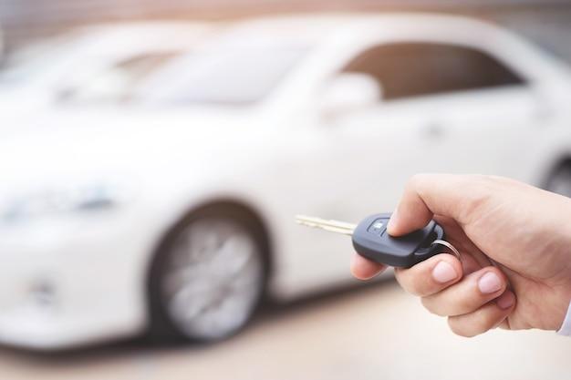Sprzedawca otwiera i zamyka drzwi samochodu kluczykiem. dla bezpieczeństwa
