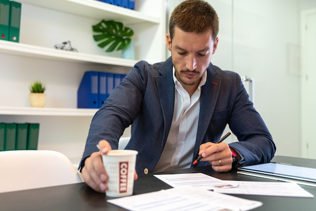 Sprzedawca patrząc na polisę ubezpieczeniową w swoim biurze