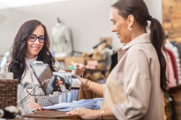 Sprzedawca patrzy na terminal płatniczy po tym, jak klientka zapłaciła w sklepie z modą.