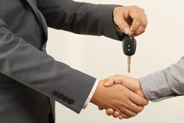 Sprzedawca podaje klientowi rękę i wręcza mu kluczyki do samochodu.