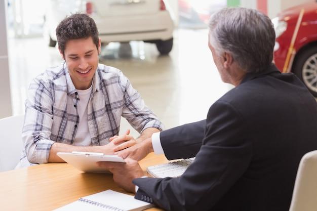 Sprzedawca pokazujący klientowi, gdzie podpisać umowę