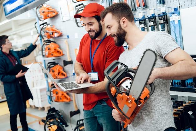 Sprzedawca pokazuje klientowi nową piłę łańcuchową