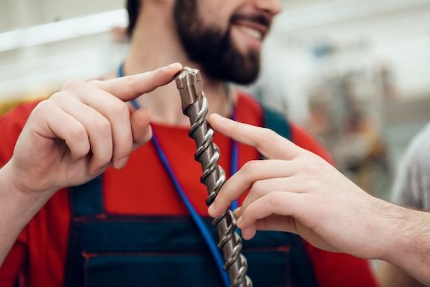 Sprzedawca pokazuje klientowi nowe gigantyczne wiertło.