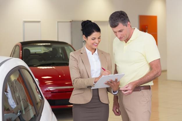 Sprzedawca pokazuje schowek podpisywać klient